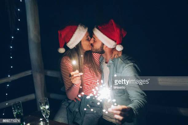Young couple on the beach with Santa Claus caps