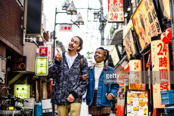 東京の休暇中の若いカップル街の通りを探索 - 観光 ストックフォトと画像