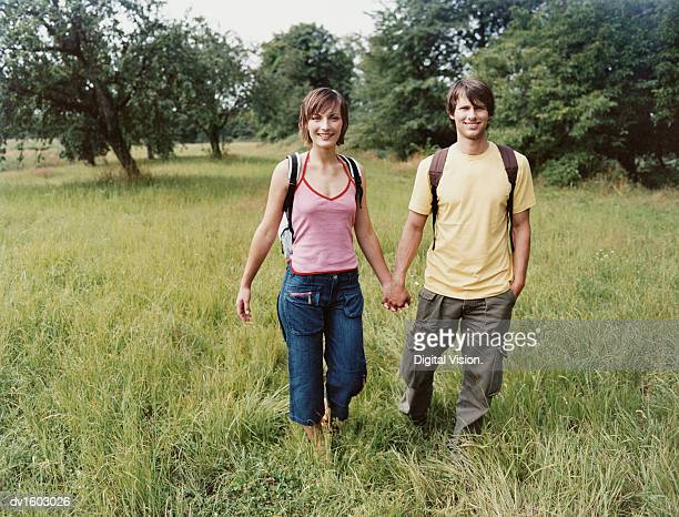 young couple on vacation walking hand in hand in a field - cargo pants stock photos and pictures