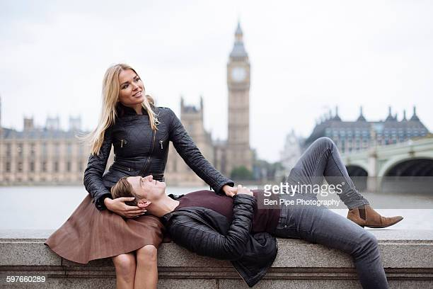 Young couple on wall in front of Big Ben, London, England, UK