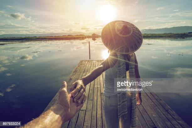 young couple on wooden lake pier in myanmar, follow me to - wonderlust stock pictures, royalty-free photos & images