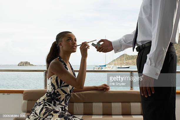 Young couple on yacht, man lighting woman's cigarette