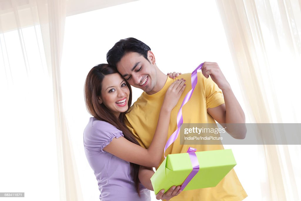 Young couple opening a gift : Stock Photo