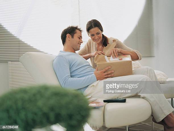 Young Couple Opening a Parcel Sitting on a Sofa in Their Sitting Room