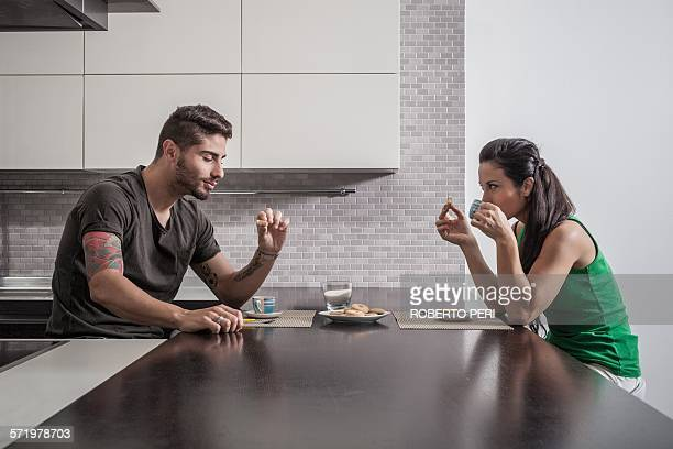 Young couple opposite each other having breakfast in kitchen