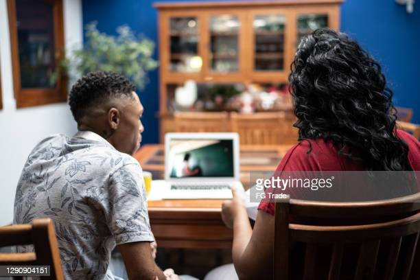 young couple or siblings using laptop watching a video classes at home - mindzoom 2 stock pictures, royalty-free photos & images