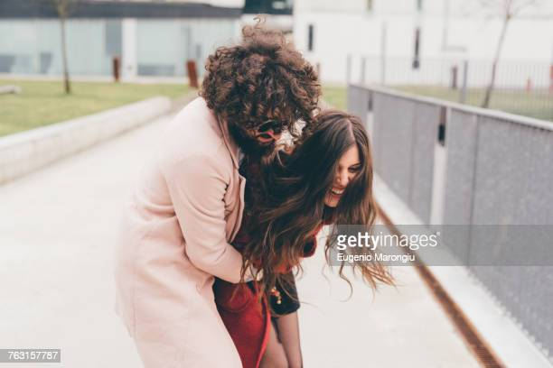 young couple outdoors, fooling around, young man hugging young woman, laughing - kitzeln stock-fotos und bilder