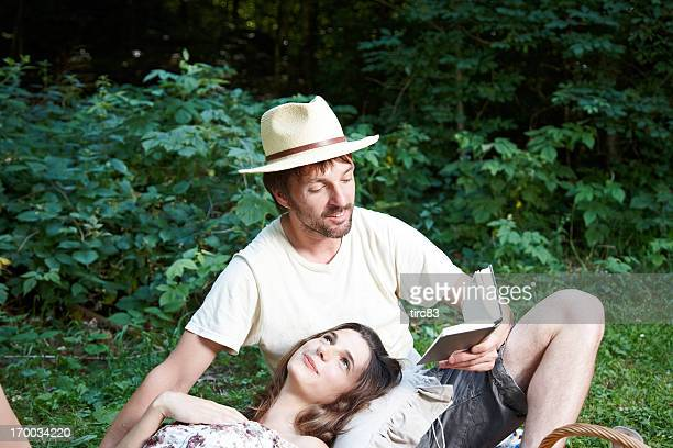 Young couple outdoors having picnic on blanket