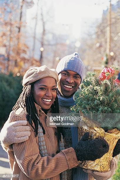 Young Couple Outdoors Holding a Small Christmas Tree