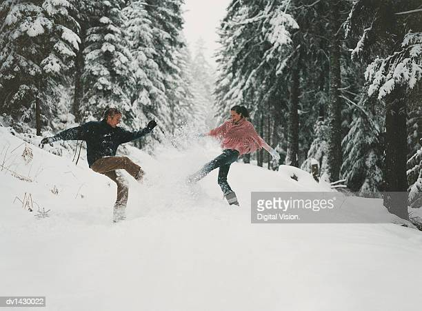 young couple outdoors kicking snow in a forest clearing - snow boot stock photos and pictures