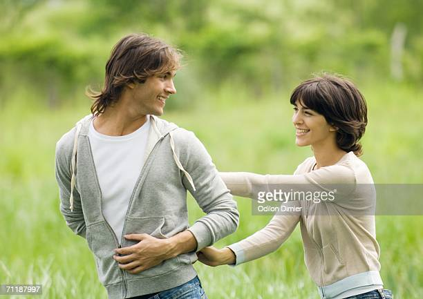 Young couple outdoors, man looking at woman over shoulder
