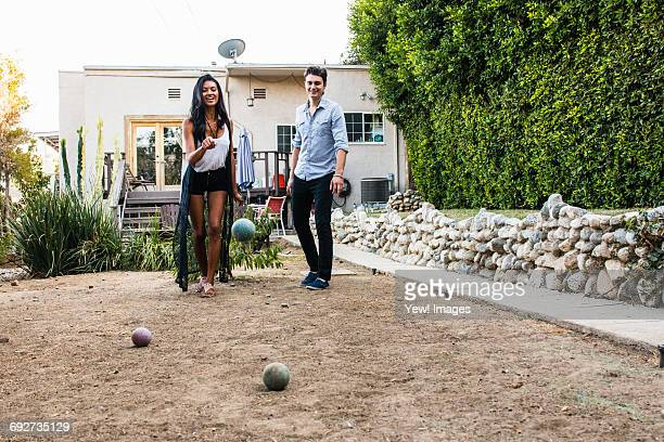 young couple outdoors, playing boule - ブール ストックフォトと画像