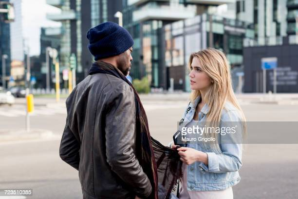 Young couple outdoors, standing face to face, serious expressions