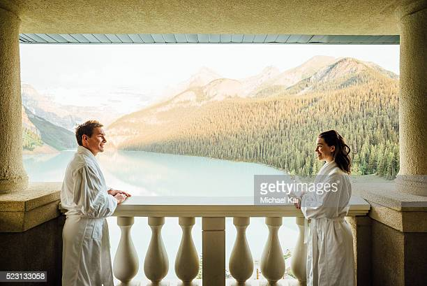 young couple overlooking lake louise on balcony, banff national park, alberta, canada - chateau lake louise stock photos and pictures