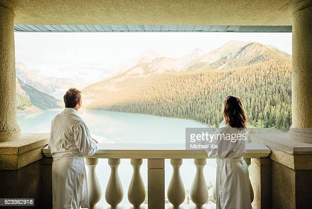 Young couple overlooking Lake Louise on balcony, Banff National Park, Alberta, Canada