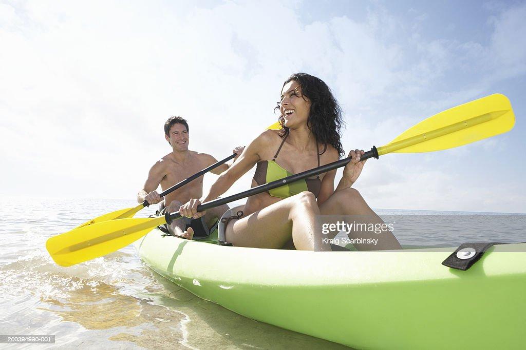 Young couple paddling canoe in bay, smiling : Bildbanksbilder