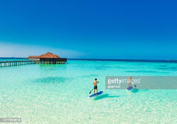 young couple paddling on paddleboard in tropical ocean - maldives stock pictures, royalty-free photos & images