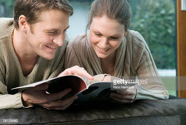young couple paging through a magazine - glass magazine stock photos and pictures