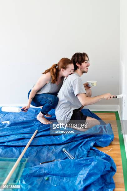 Young couple painting living room in first appartement.
