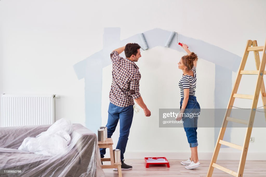Young couple painting the interior wall in their new apartment : Stock Photo