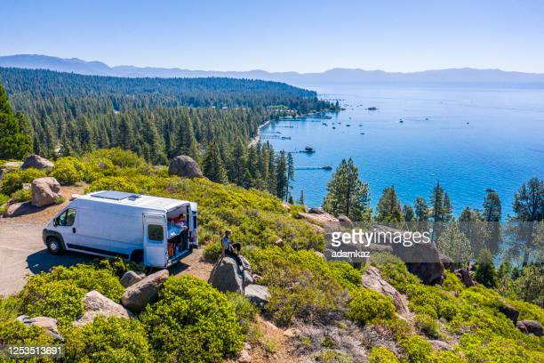 young couple parked van at a viewpoint of lake tahoe - adamkaz stock pictures, royalty-free photos & images