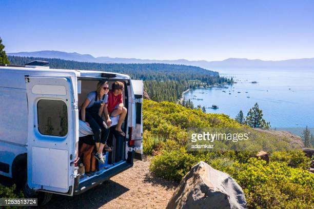young couple parked van at a viewpoint of lake tahoe - camper trailer stock pictures, royalty-free photos & images