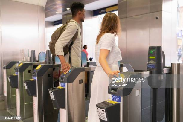 young couple passing subway gate with electronic tickets - tube stock pictures, royalty-free photos & images