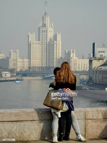 Young couple passionately kissing on a bridge in Moscow, with a Stalinist monument in the back.