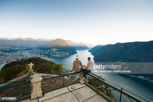 Young couple pause on balcony above lake, valley