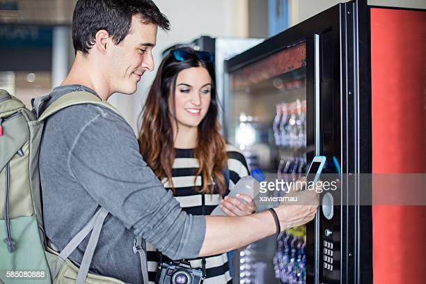 Young couple paying with mobile phone the soft drink