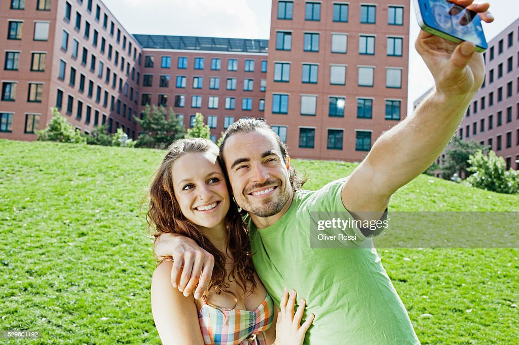 Young couple photo messaging from park : Foto stock