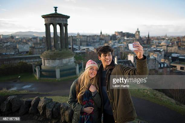 a young couple photograph themselves on calton hill with the background of the city of edinburgh, capital of scotland - edinburgh scotland stock pictures, royalty-free photos & images