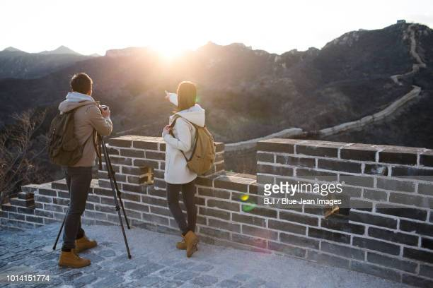 young couple photographing on the great wall - pointing at camera stock photos and pictures