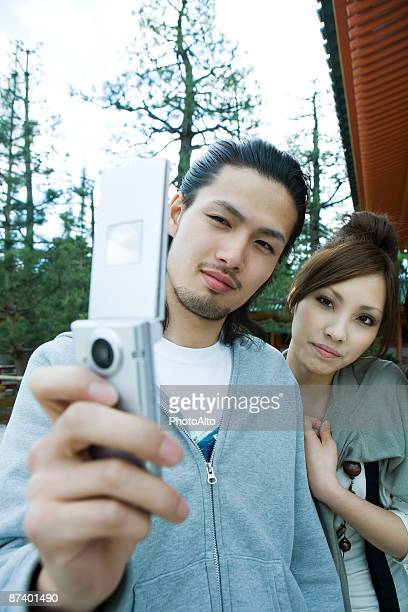 Young couple photographing selves with cell phone