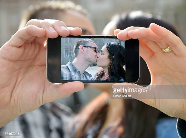 young couple photographing themselves kissing