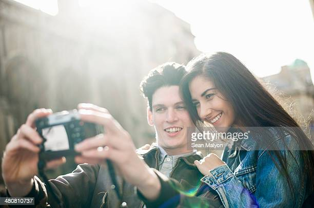 young couple photographing themselves - sean malyon stock pictures, royalty-free photos & images