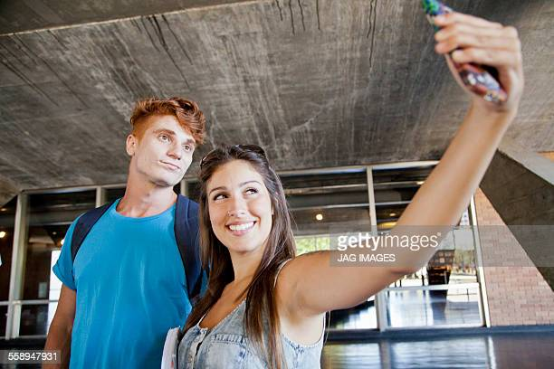 Young couple photographing themselves with phone