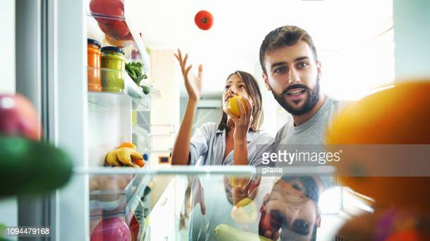 young couple picking up some fruits and veggies from the fridge. - domestic kitchen stock pictures, royalty-free photos & images