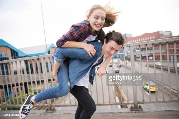 Young Couple Piggyback On Bridge