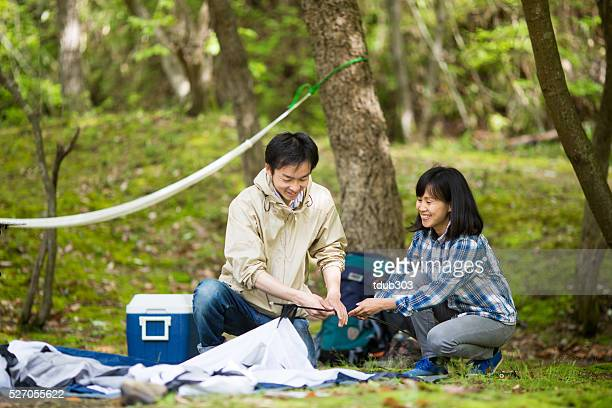 Young couple pitching a tent while camping