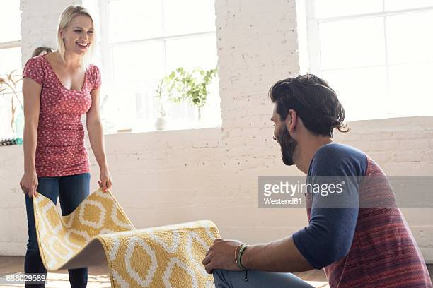 Young couple placing carpet in a loft