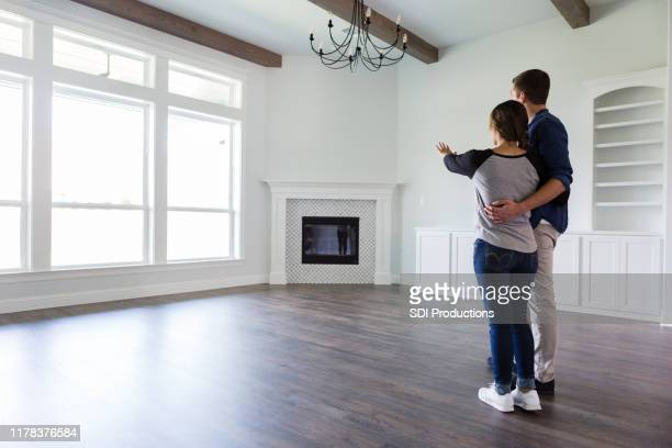 young couple plan home decor in new home - casal heterossexual imagens e fotografias de stock