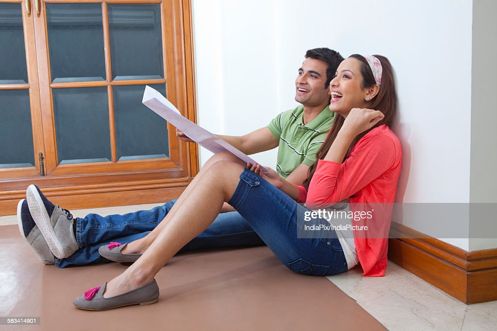 Young couple planning lay out of their house : Stock Photo