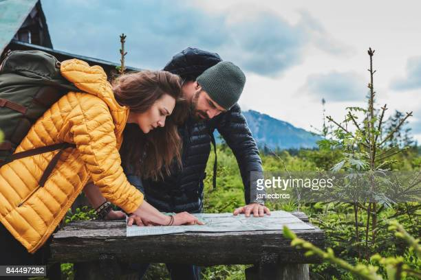 young couple planning their trip with map - wilderness stock pictures, royalty-free photos & images