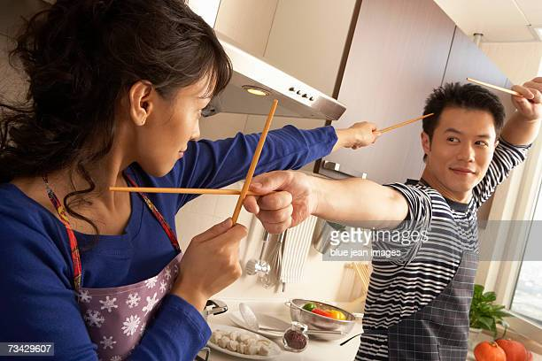 A young couple play fight with chopsticks in the kitchen.