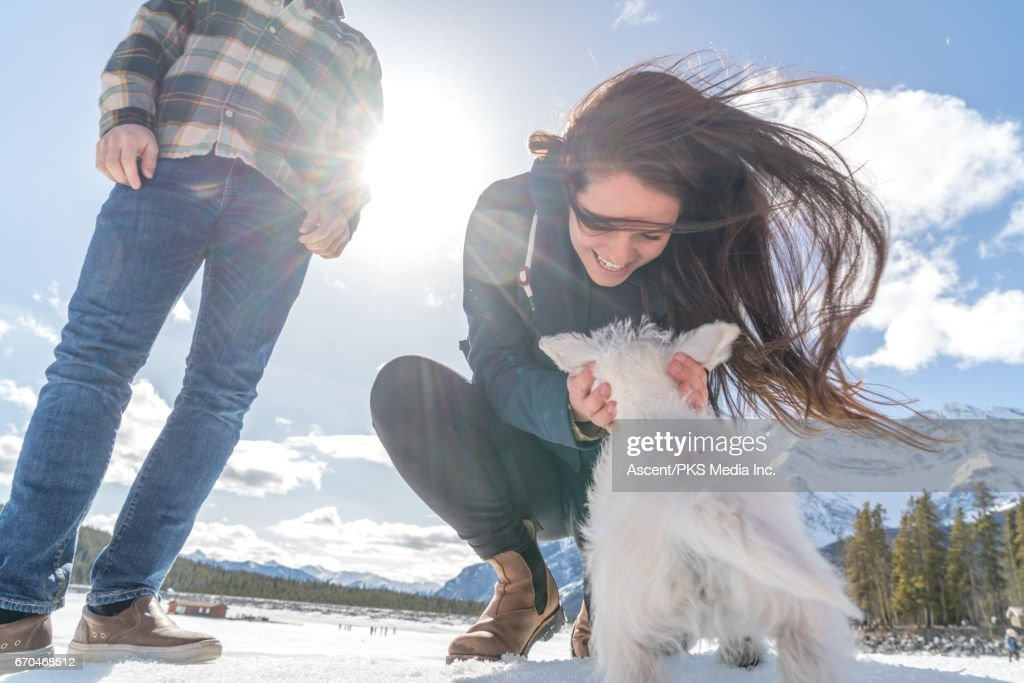 Young couple play with dog, in snowy mountain setting : Stock Photo