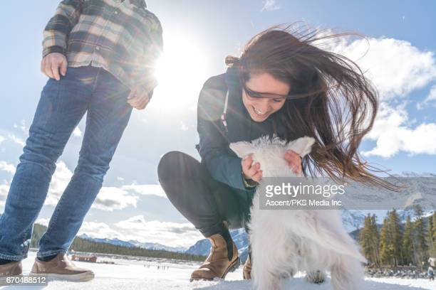 Young couple play with dog, in snowy mountain setting