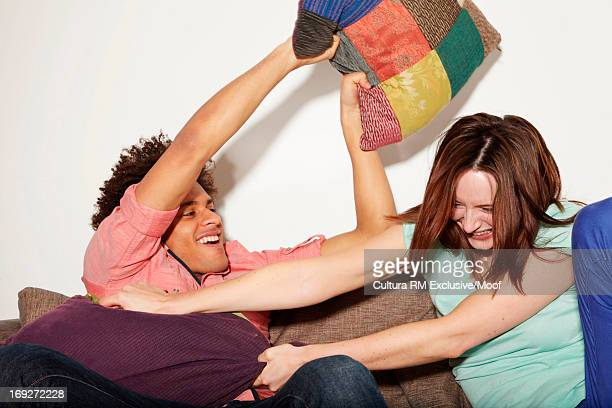 young couple playfighting with cushions - female wrestling holds stockfoto's en -beelden