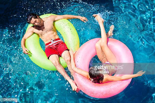 young couple playing around in pool on inner tubes