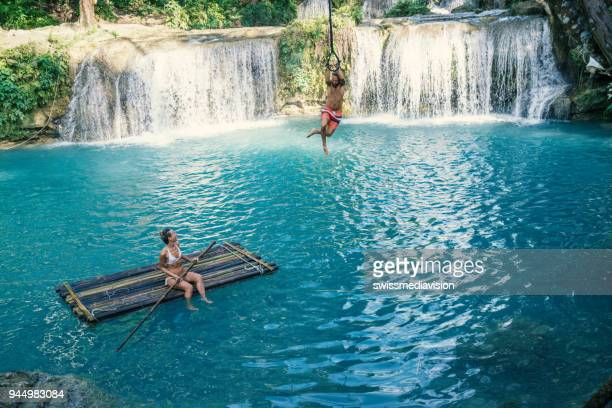 Young couple playing at beautiful waterfall in the Philippines